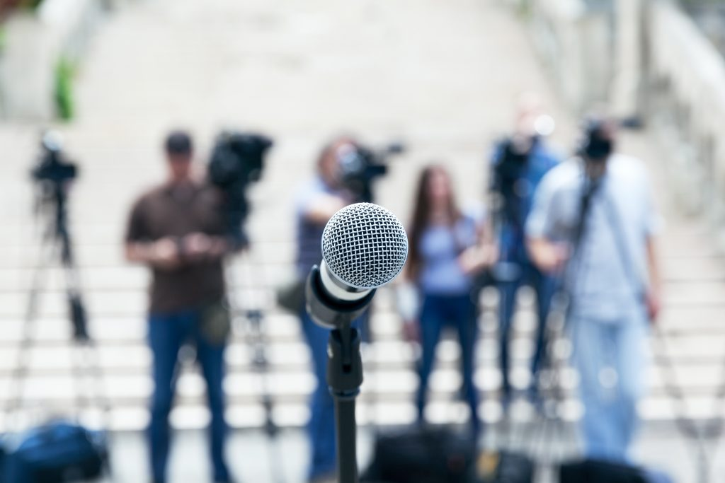 Microphone in focus against blurred camera operators and journalists at news conference