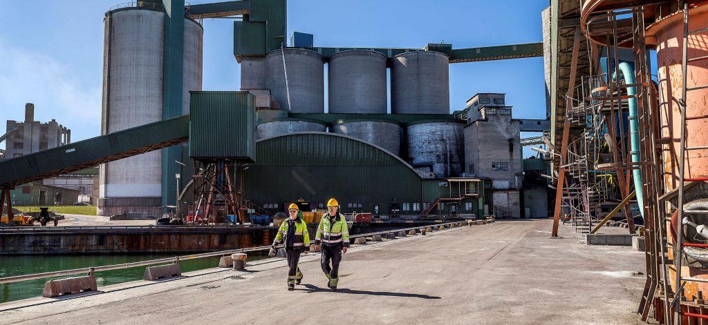Personer framför cementfabrik