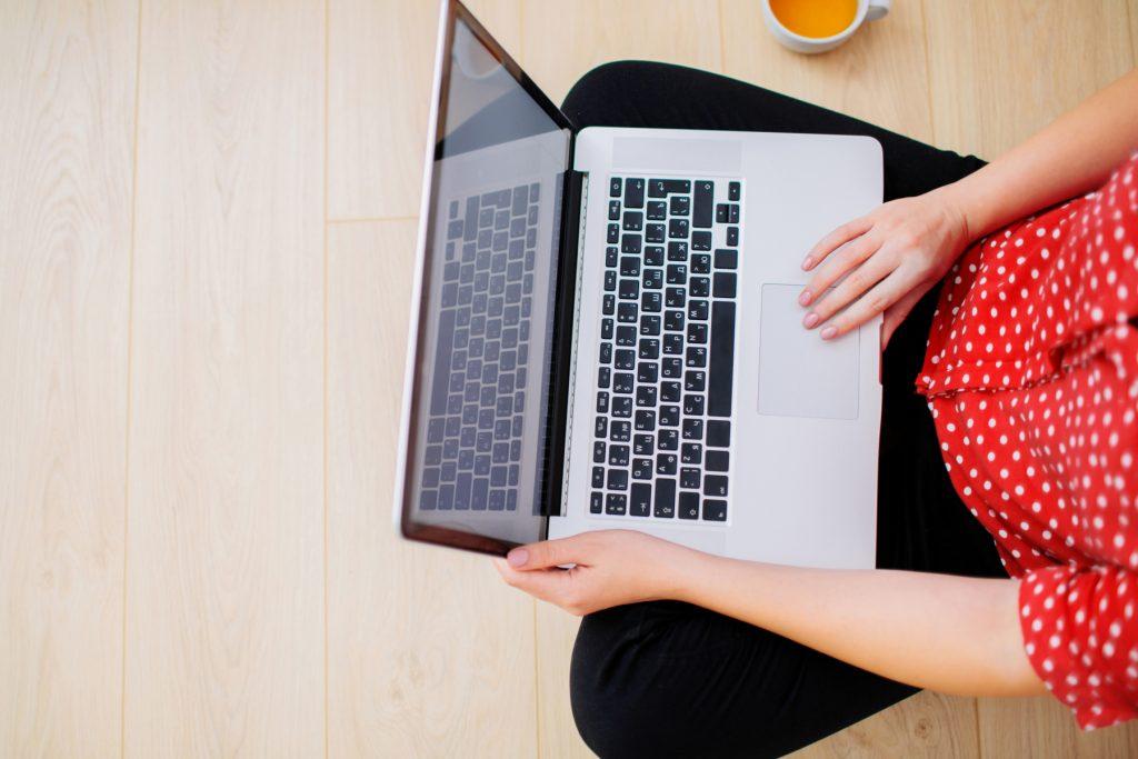 Kvinna (fotograferad uppifrån) arbetar med laptop