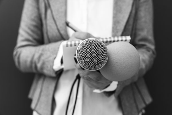 Reporter på presskonferens, skriver anteckningar, håller mikrofon. Mediehändelse.